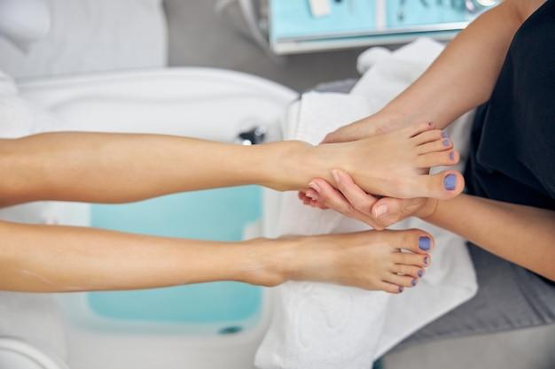 スパサロンでプロによるペディキュア後のマッサージを楽しんでいる女性の足のクローズアップの上面図