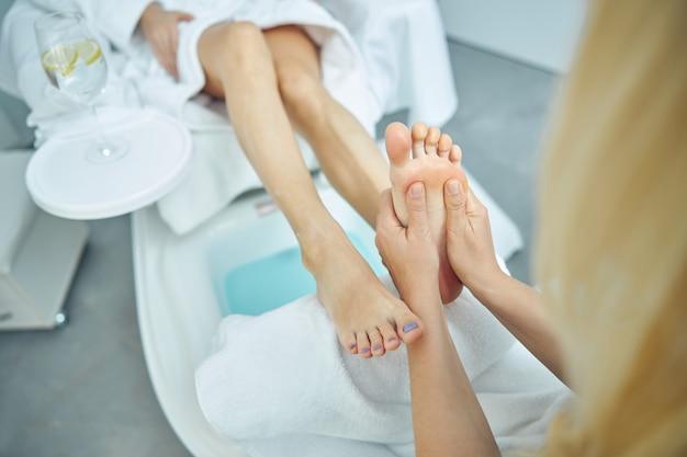 彼女がスパサロンでプロの手でそれらをリラックスしている間、上面図は女性の足のクローズアップ