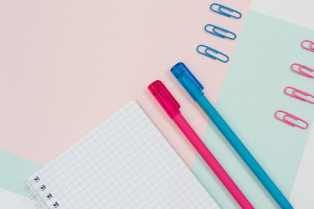 위쪽 보기는 분홍색 및 파란색 바클그라운드에 열려 있는 빈 나선형 메모장, 펜 및 종이 클립의 클로즈업 사진