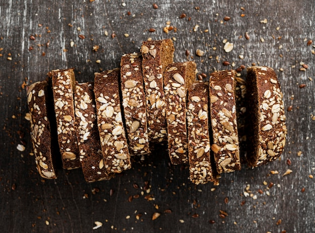 Top view close-up slices of whole-grain bread and wooden background