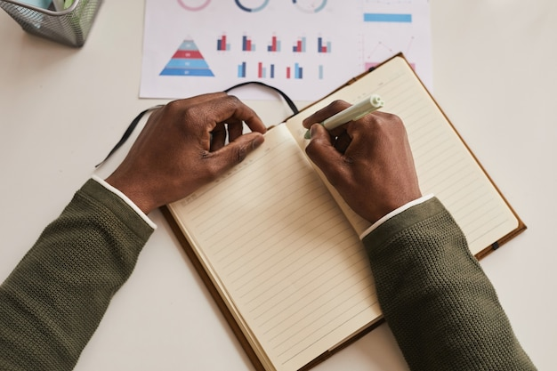 Top view close up of unrecognizable man writing in planner while working at desk in office, focus on male hands holding pen, copy space