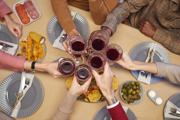 Top view close up of unrecognizable young people clinking glasses sitting at table together and enjoying thanksgiving dinner with friends and family,