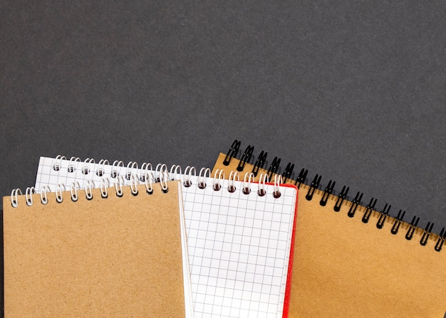 Top view of closed black cover notebook with pencil on white desk background