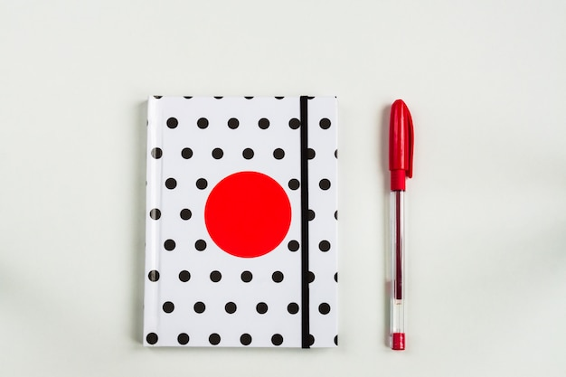 Top view of closed polka dot cover notebook with red pen on white desk background