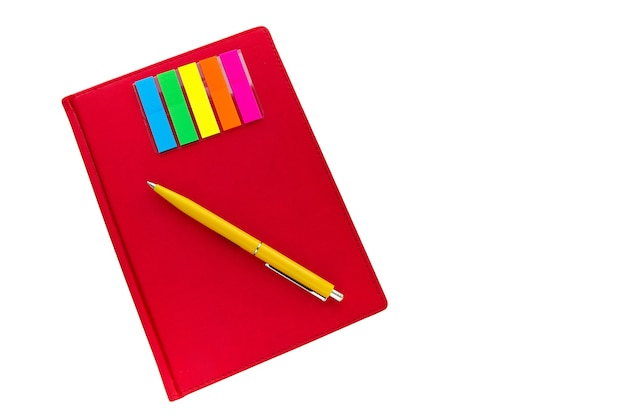 Top view of closed red notebook, yellow pen, colored bookmarks on white background