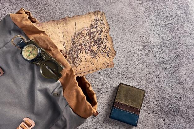 Primo piano vista dall'alto di una bussola posta su un tessuto colorato accanto a un'antica mappa e un portafoglio
