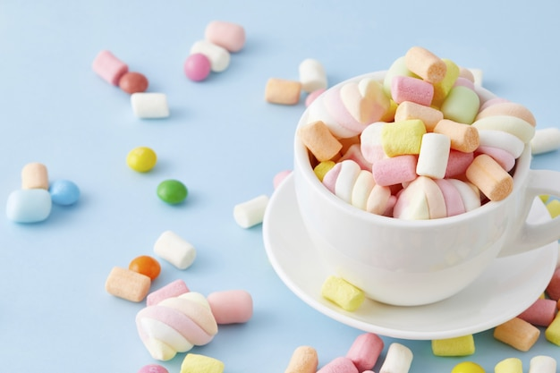 Top view closeup of a cup filled with colorful marshmallows isolated on a blue surface