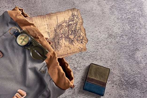 古代の地図と財布の横にあるカラフルな布の上に置かれたコンパスの上面図のクローズアップ