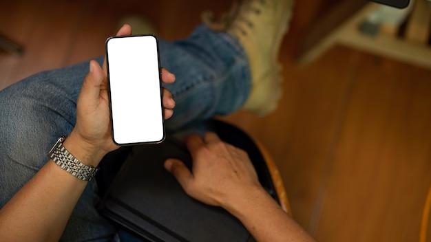 Крупным планом вид сверху на хипстера-фрилансера-мужчину, использующего свой мобильный макет пустого экрана смартфона