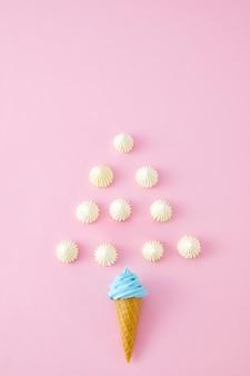 ピンクの壁に分離された渦巻きマシュマロ、スキットルズ、アイスクリームコーンの上面図のクローズアップ