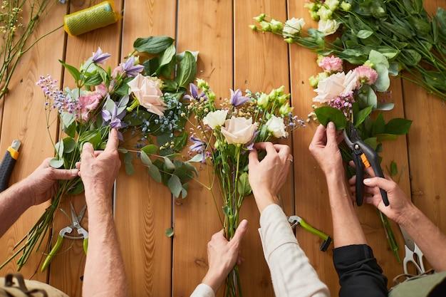 Крупным планом вид сверху трех флористов, расставляющих цветочные композиции на деревянном столе в уютной мастерской c ...