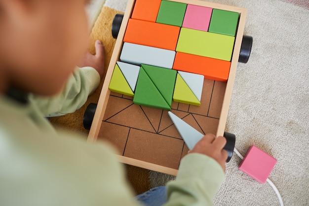 自宅の床に座っている間、木のおもちゃで遊んでいる認識できないアフリカ系アメリカ人の子供の上面のクローズアップ、コピースペース