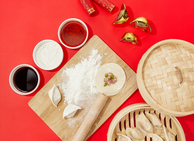 Top view closeup of raw dumplings being made on a cutting board with flour on a red background