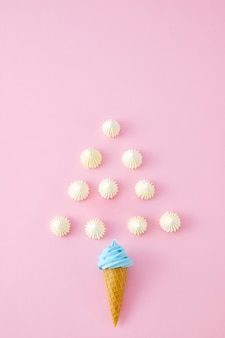 Top view closeup of swirled marshmallows, skittles and ice cream cones isolated on a pink wall