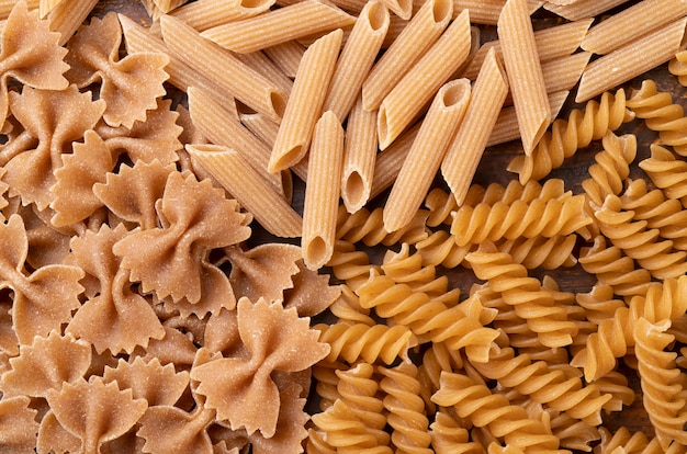 Top view, closeup of whole wheat farfalle, penne and fusilli pasta.