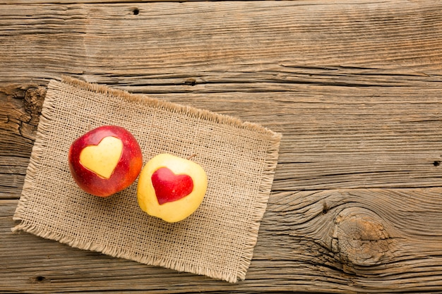 Top view of cloth and apple with fruit heart shapes and copy space