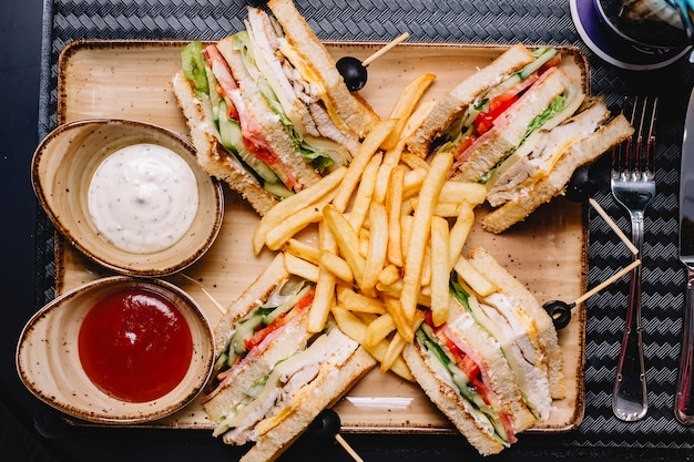 Top view of club sandwich served with french fries ketchup and mayonnaise