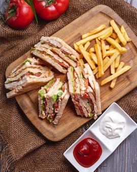 Вид сверху клубный бутерброд с картофелем фри, кетчупом с майонезом и помидорами
