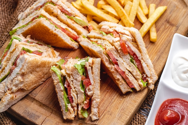 Top view club sandwich with french fries ketchup with mayonnaise