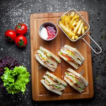 Top view club sandwich with sauce ketchup and mayonnaise and french fries in wooden serving board on dark stone background