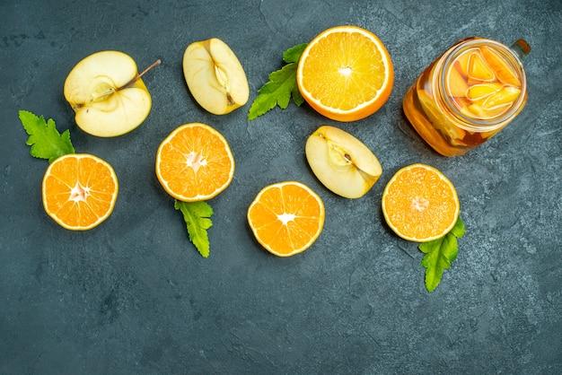 Vista dall'alto arance e mele tagliate cocktail su sfondo scuro isolato