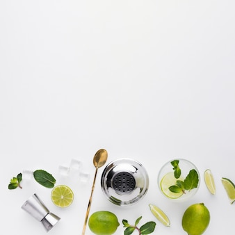 Top view of cocktail essentials with lime and copy space