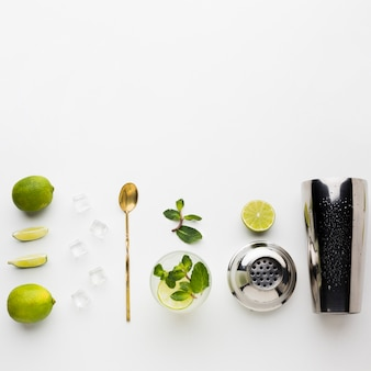 Top view of cocktail essentials with shaker and lime