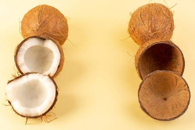 Noci di cocco di una vista superiore affettate con dolce fresco latteo delle bucce isolato sulla crema colorata