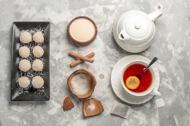 白い表面にお茶のカップとココナッツケーキの上面図