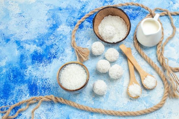 Vista dall'alto ciotola di polvere di cocco palle di cocco corda cucchiai di legno ciotola di latte su sfondo bianco blu