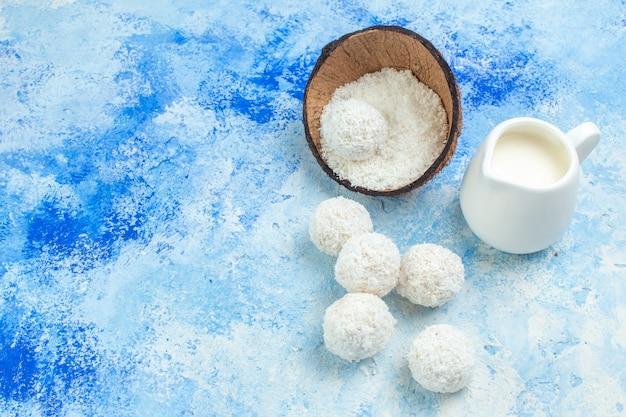 Vista dall'alto ciotola di polvere di cocco ciotola di latte palle di cocco corda cucchiai di legno su sfondo bianco blu
