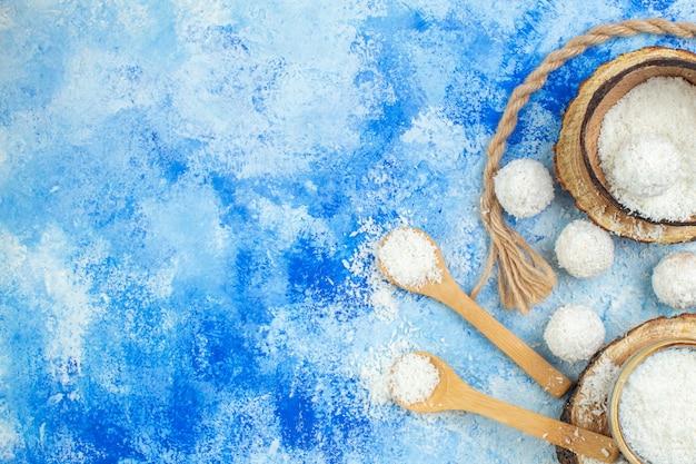 나무 판자에 있는 상위 뷰 코코넛 가루 그릇 코코넛 눈덩이는 파란색 흰색 배경에 나무 숟가락을 묶고 무료 장소를 제공합니다.