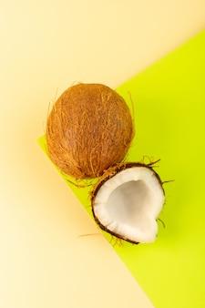 Una vista dall'alto noci di cocco intero latteo fresco morbido isolato sul color crema-pistacchio