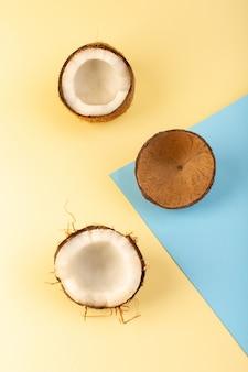 Una vista dall'alto noci di cocco intere e affettate latteo fresco dolce isolato sul color crema-blu-azzurro