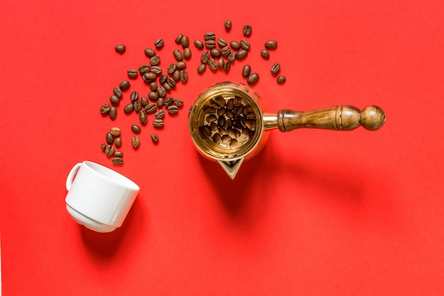 Top view of coffe beans in  cezve (traditional turkish coffee pot), whte cup on red background.