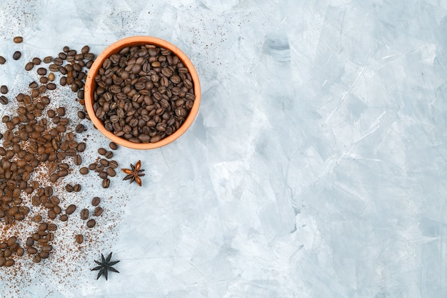 Top view coffee beans in a bowl with spices on grunge background