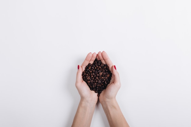 Top view of coffee beans in female hands on a white background