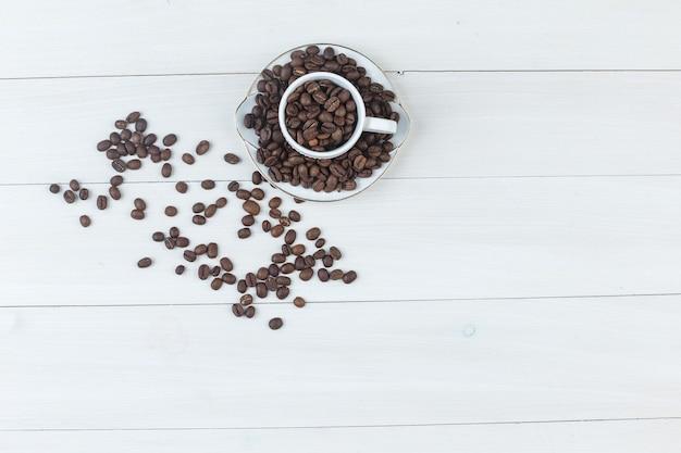 Кофейные зерна взгляда сверху в чашке и поддоннике на деревянной предпосылке взгляд сверху. горизонтальный