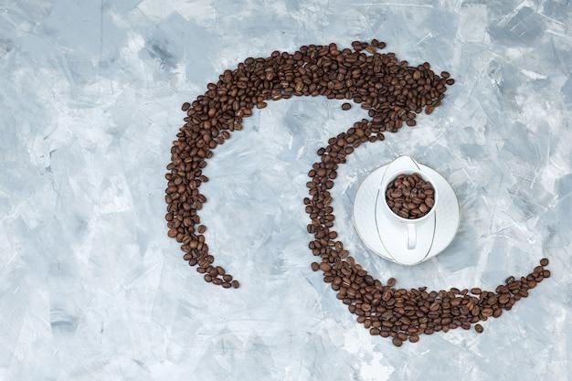 灰色の石膏の背景にカップのトップビューコーヒー豆。水平