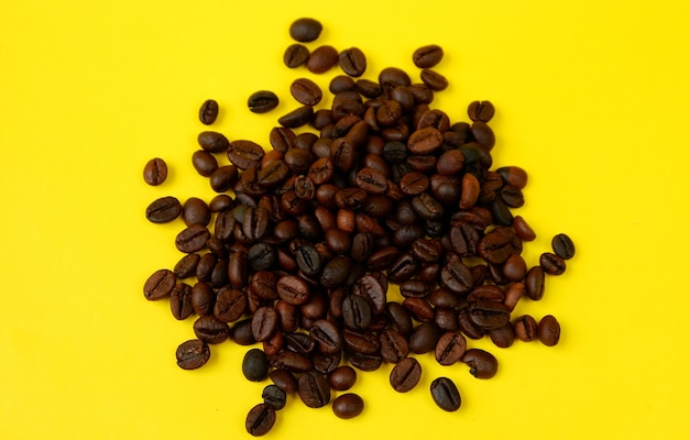 Top view of coffee beans isolated on a yellow background