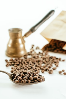 Top view of coffee beans scatered around, a cardboard bag, a spon and a rustic coffee maker