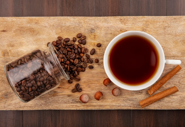 Top view of coffee beans spilling out of glass jar and cup of tea with cinnamon and nuts on cutting board on wooden background