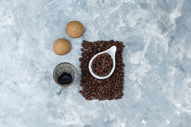 Top view coffee beans in white porcelain jug with cookies, cup of coffee on blue marble background. horizontal