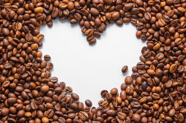 Кофейные зерна взгляд сверху с пустой формой сердца на белой предпосылке. горизонтальный