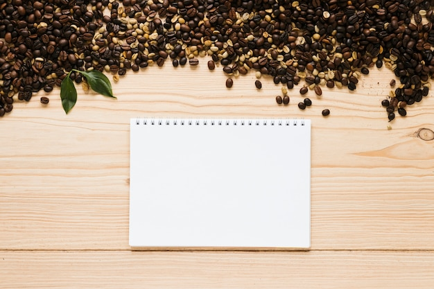 Top view of coffee beans with notebook mock-up