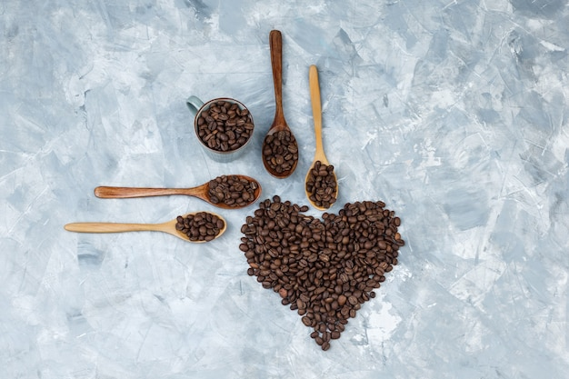 Top view coffee beans in wooden spoons and cup on grey plaster background. horizontal