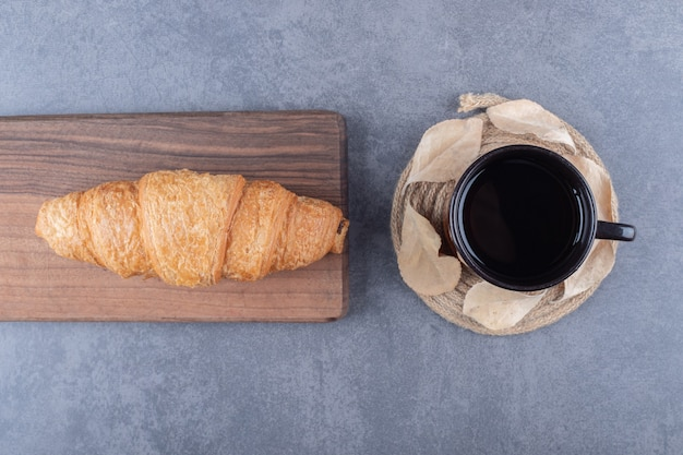 Top view of coffee and croissants. classic french breakfast on grey background.