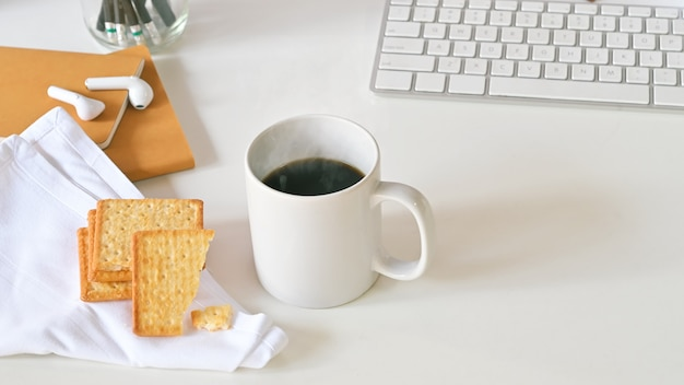 Top view of coffee cup, biscuits, white button keyboard, pencil holder, notebook and white napkin on white desk.