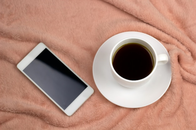 Top view coffee cup and cell phone  on a pink blanket