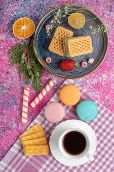 Top view of coffee cup, cookie sandwiches, crackers and marshmallows